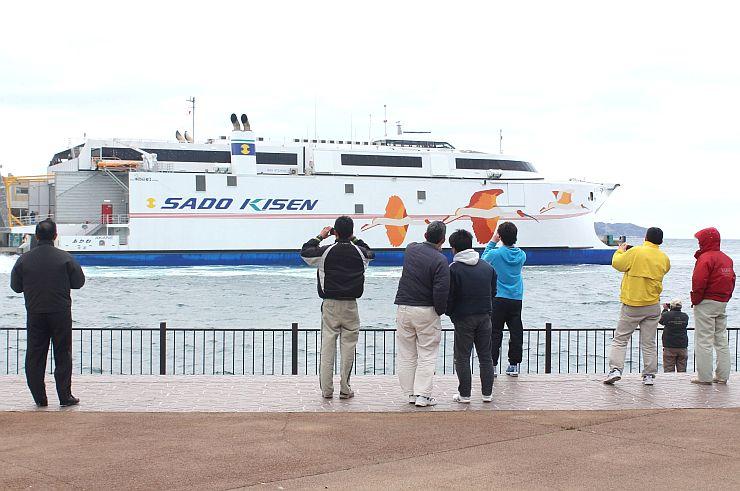 地元の住民が見守る中、小木港に到着したあかね=8日、佐渡市小木町