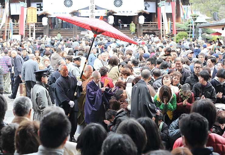 御開帳開幕後、最初の土曜日を迎え、参拝者でにぎわう長野市の善光寺。頭に数珠を当ててもらう「お数珠頂戴」に大勢が並んだ=11日午前9時51分