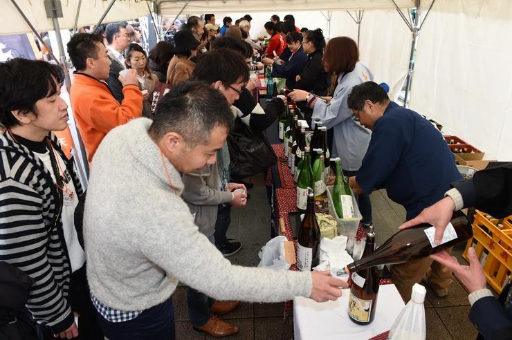 酒をついでもらい、違いを味わう参加者たち=11日午後、松本市中央1の花時計公園