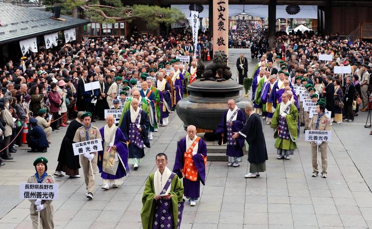 回向柱前での法要後、本堂へ向かう全国善光寺会の住職ら=11日午後2時38分、長野市の善光寺