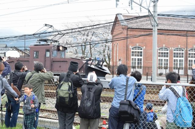 レンガ館、桜との共演を狙ってラッセル車を撮るファンら=11日、永平寺町東古市