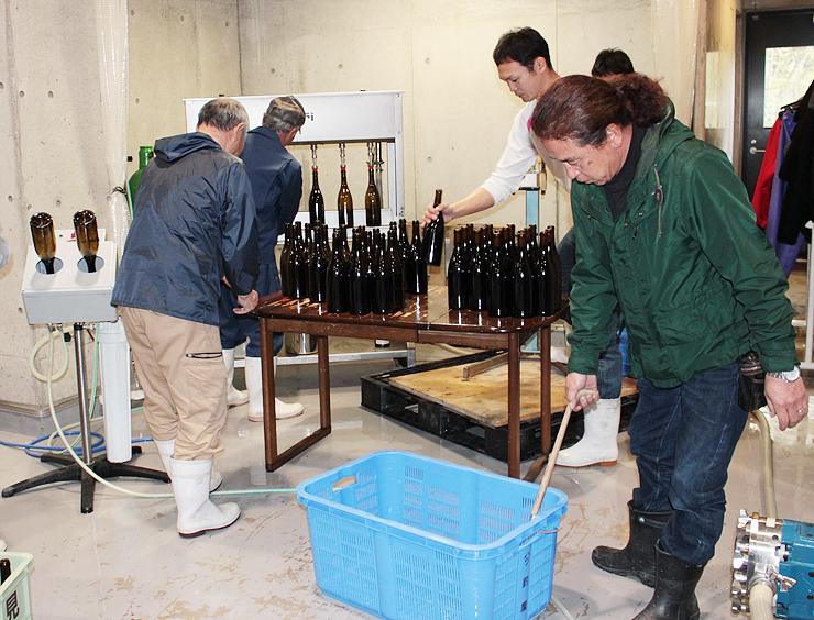熟成させたメルローを瓶詰めするスタッフと余川地区の住民=セイズファーム