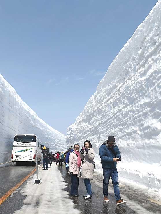 迫力ある「雪の大谷」を散策する観光客=16日午前10時45分、富山県立山町室堂付近