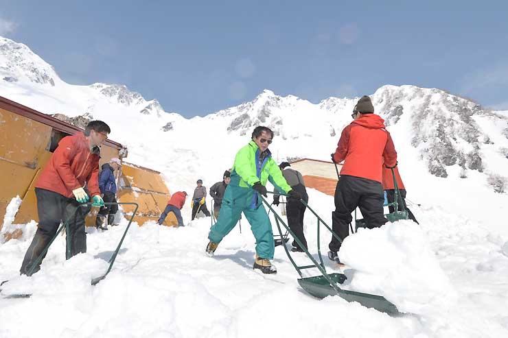 涸沢ヒュッテの営業開始に向けて、雪に埋まった建物を掘り出す従業員ら=16日午前9時15分、北アルプス・涸沢