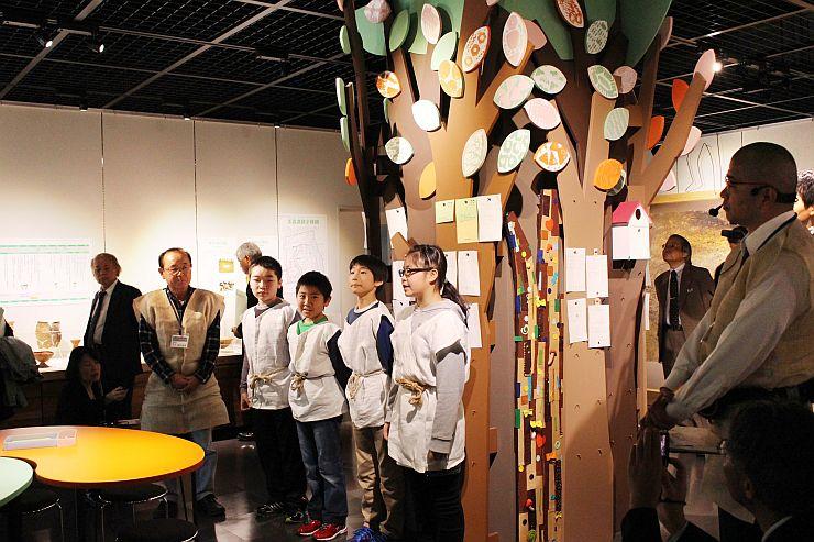 「謎解きの木」の前で質問を発表する小学生=16日、上越市