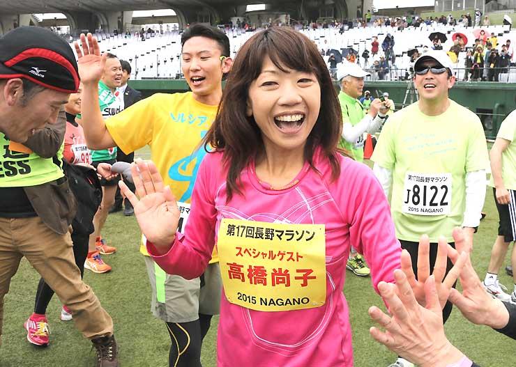 笑顔でゴール後のランナーを迎える高橋尚子さん=午後1時28分、長野オリンピックスタジアム