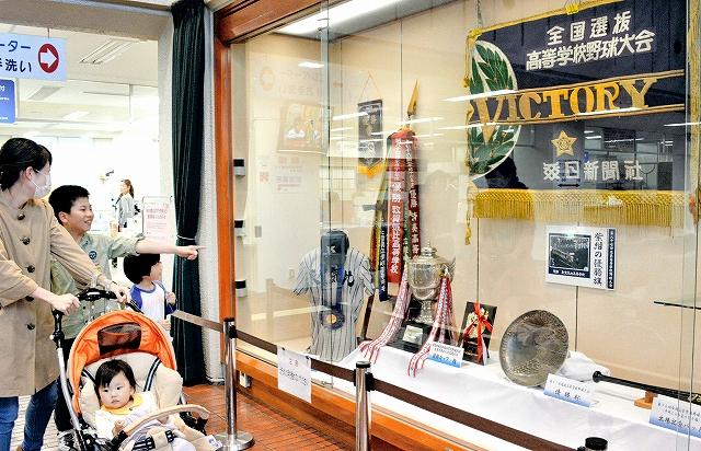 紫紺の優勝旗や敦賀気比高の名前が記されたペナントが並べられた福井県の敦賀市役所の展示コーナー=20日、同市役所