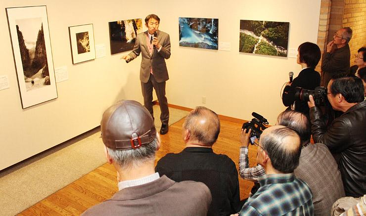 大正から昭和初期にかけてと現在の黒部峡谷をとらえた写真について解説する志水さん(中央)