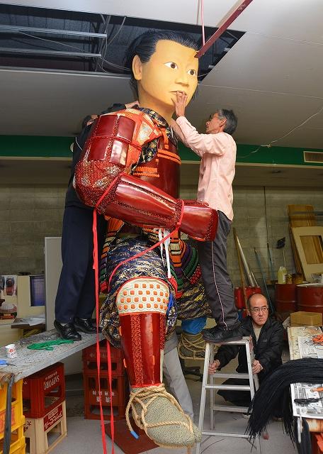 祭りに向け人形山車の仕上げ作業に取り組むメンバー=17日夜、福井県あわら市温泉5丁目