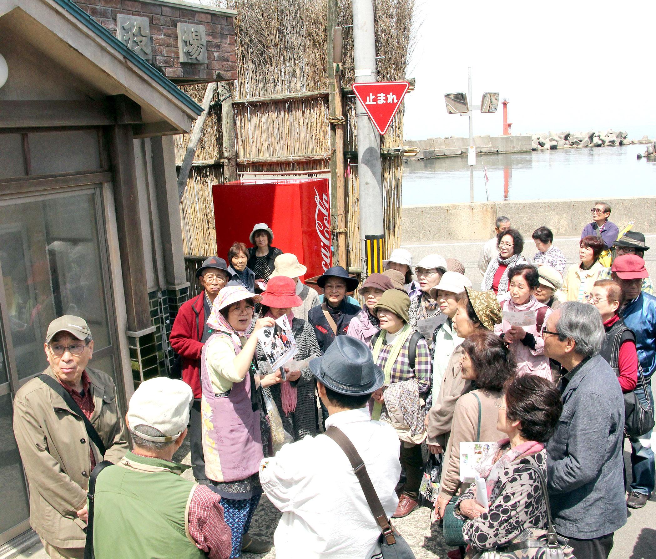 「外浦村役場」前で撮影時の話を聞く参加者=輪島市大沢町