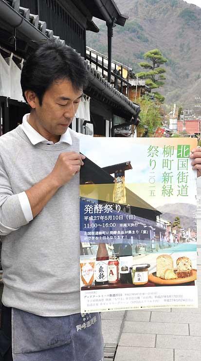 「柳町発酵祭り」のポスターを持つ岡崎さん