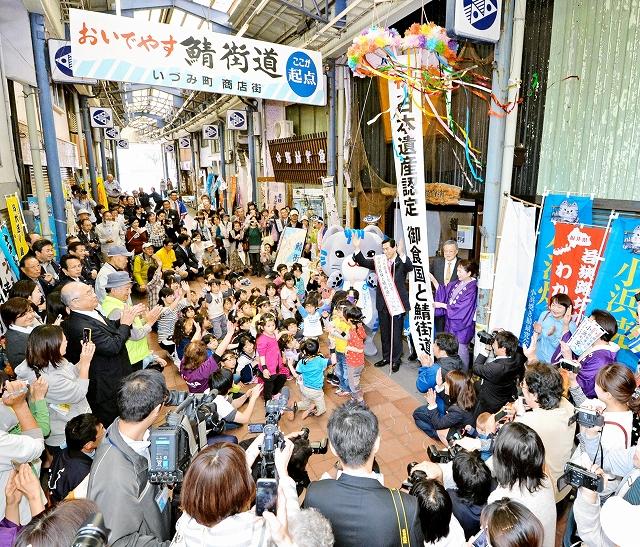 「御食国若狭と鯖街道」が日本遺産に認定され、くす玉を割り祝う関係者ら=24日、小浜市のいづみ町商店街