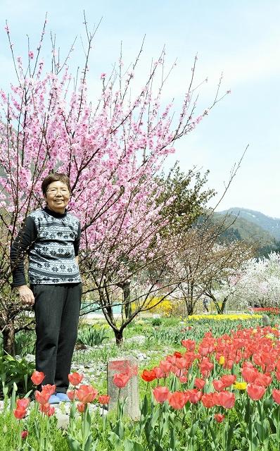 自ら育てて満開を迎えた花々に囲まれ、笑顔の林沙代子さん=24日、大野市西勝原の「勝原花桃公園」