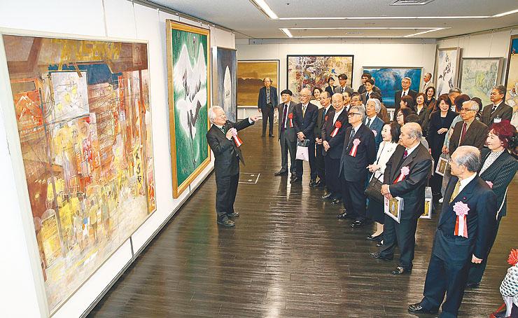 土屋事務局長(左)の解説で日本画部門の作品を鑑賞する開会式の出席者ら=県民会館