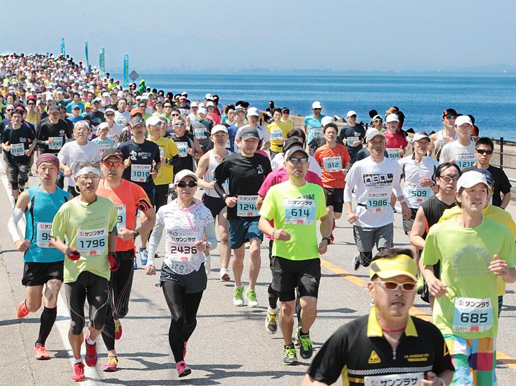 勢いよくスタートするハーフマラソンの部の出場者=魚津市のありそドーム前