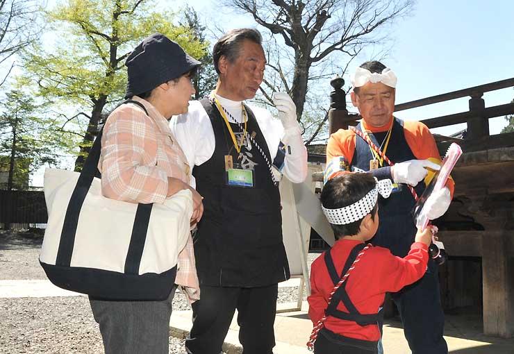 御柱祭本番の氏子の装いで観光案内する池上さん(中央)と奥村さん(右)