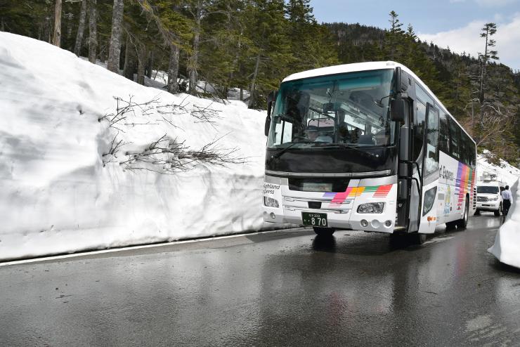 雪の壁に沿って試運転した春山バス=28日、松本市安曇