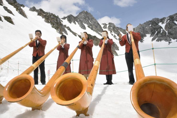 中央アルプスの山並みを背にアルプホルンを演奏する地元の愛好家=28日午前10時56分、千畳敷