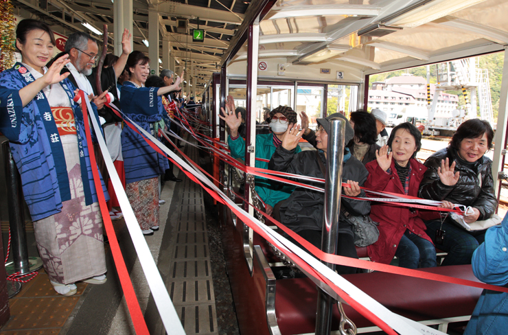 宇奈月温泉の女将らの見送りを受けて出発する乗客=黒部峡谷鉄道宇奈月駅