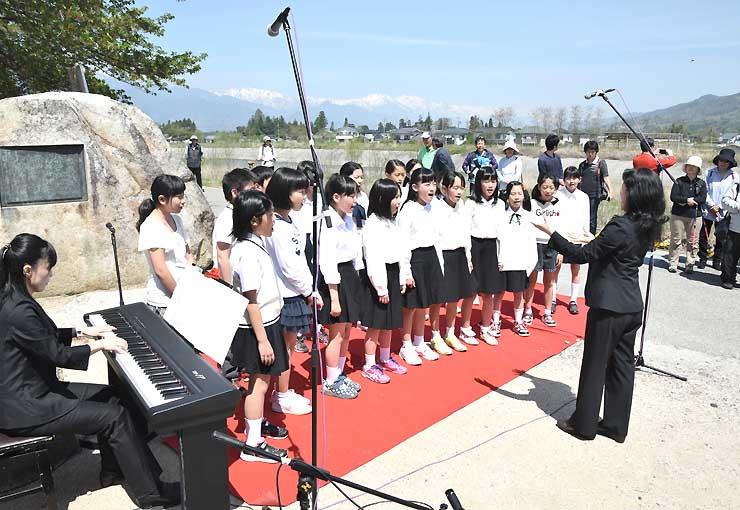 残雪の北アルプスを背景に歌を披露する小学生
