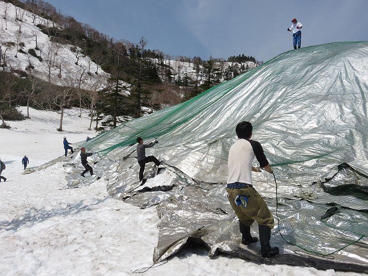 雪山にシートをかぶせた保存作業=28日、湯沢町