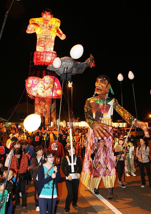 巨大人形(手前)に先導された文久の大行燈(奥)の引き回し=JR福野駅前