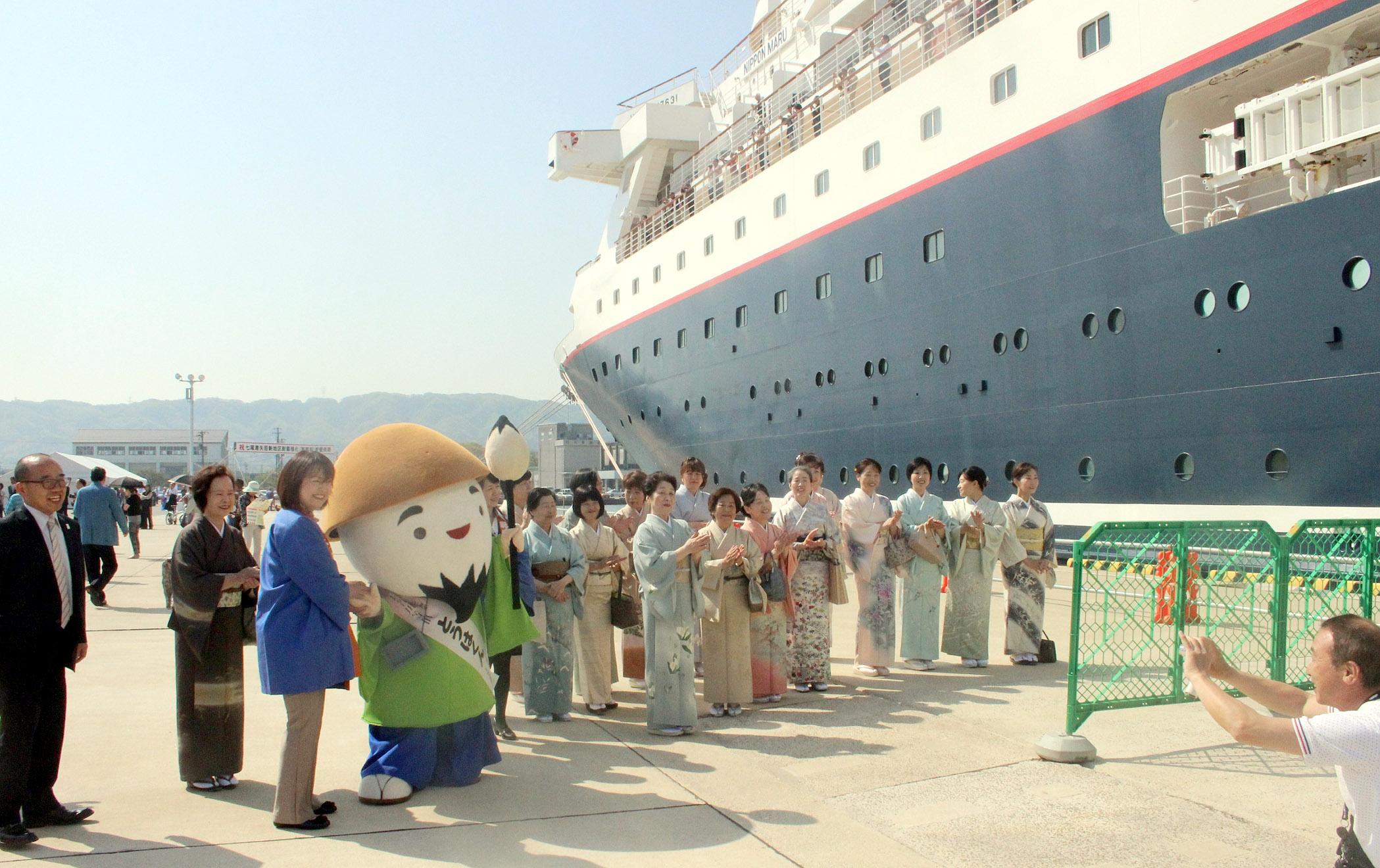 とうはくんと記念撮影するにっぽん丸の乗客=1日午前9時10分、七尾港矢田新第1埠頭