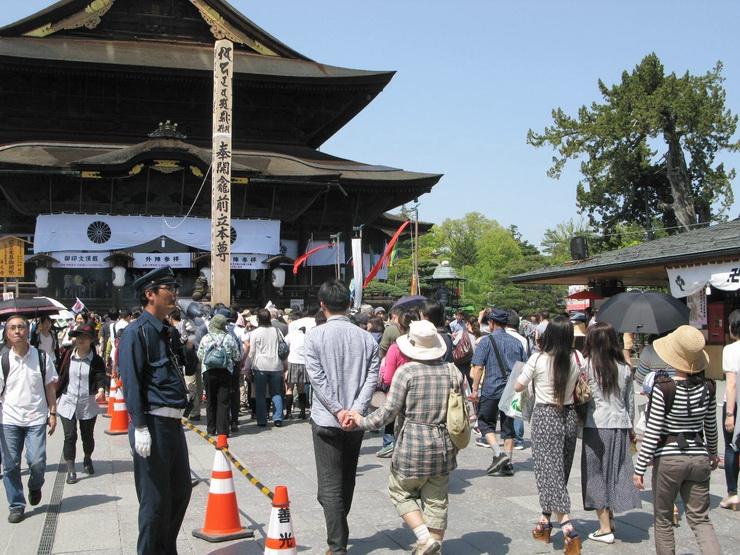 善光寺本堂前の回向柱に向かう参拝者らを誘導する警備員。午後は待ち時間がぐっと減る