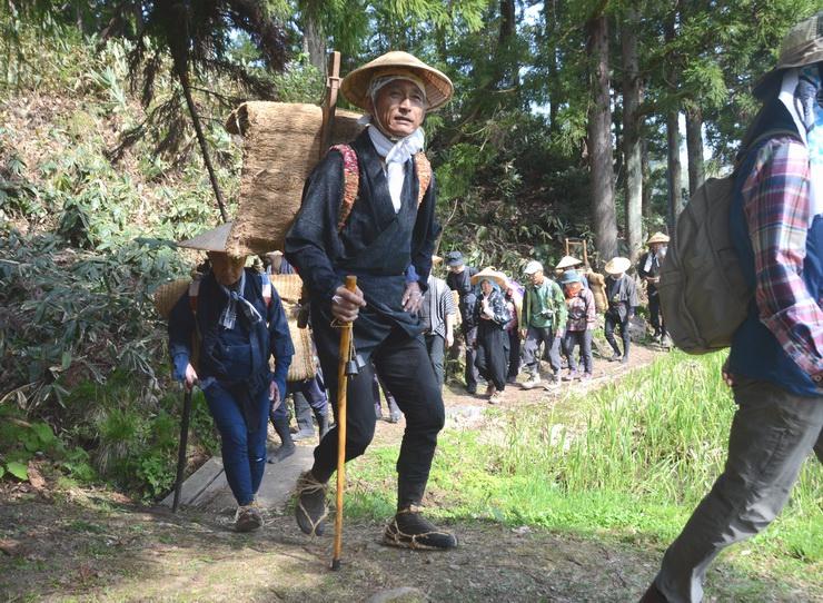 かつて塩を運んだ歩荷の服装で山道を歩く参加者=3日、小谷村