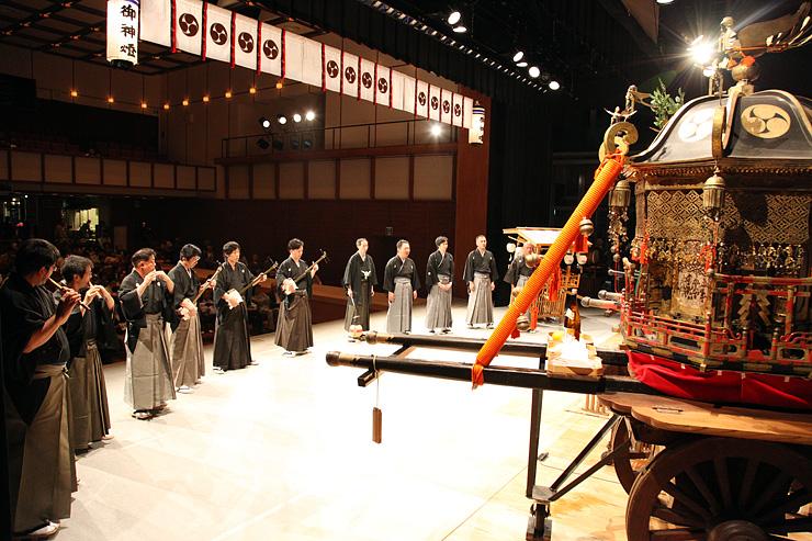 神輿の前に並び、庵唄を奉納する出丸町の若連中=南砺市城端伝統芸能会館じょうはな座