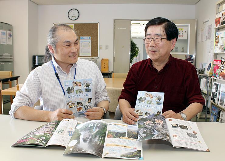 立山黒部ジオパークを紹介する冊子「ねこまた君が行く富山」を手にする梅嵜准教授(左)と津本さん