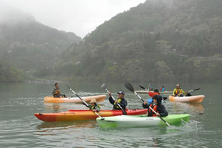 周囲に霧が立ちこめる中、カヌーを楽しむ人たち