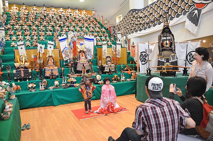 勇壮な武者人形がずらりと並ぶ15段飾りの前で、記念撮影をする子どもたち