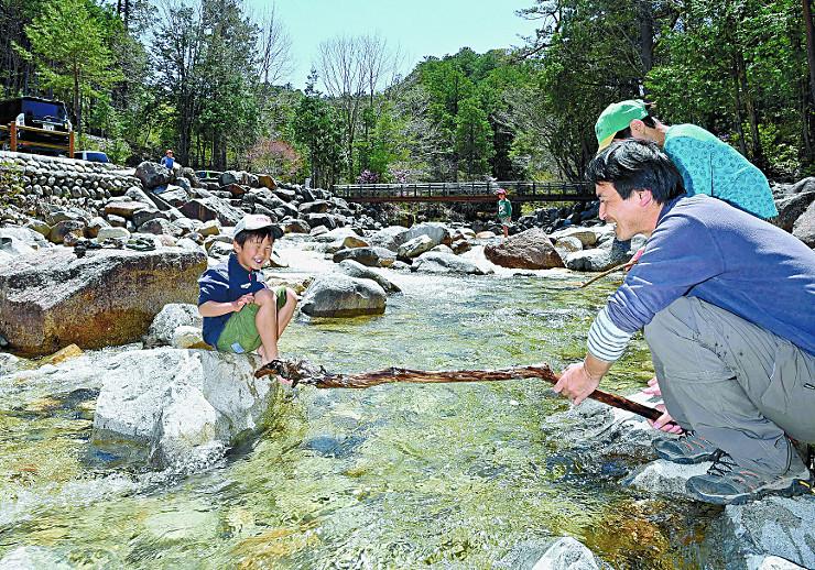 水の冷たさを感じながら川遊びする家族連れ=5日、上松町の赤沢自然休養林