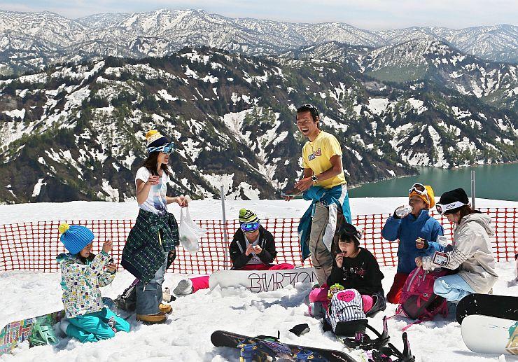 山頂からの大パノラマを見ながら休憩するスノーボーダーら=5日、魚沼市