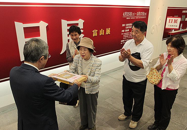 板倉社長から記念品を受け取る1万人目の青塚さん(中央)と、前後に来場した(奥左から)酒井さん、西森さん夫妻=県民会館