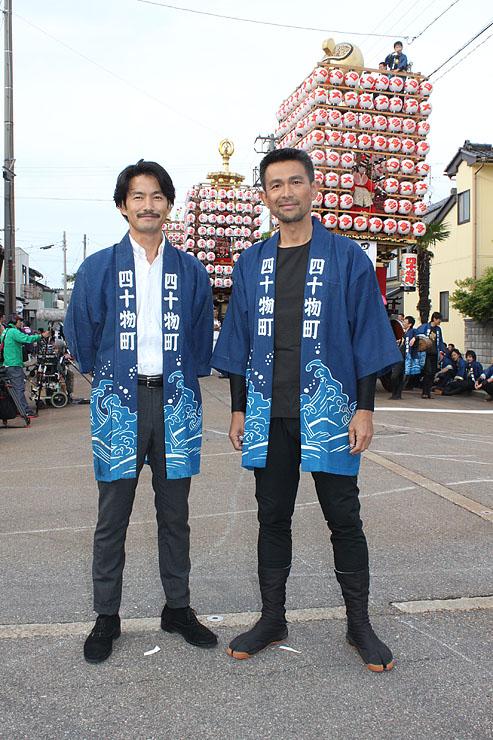 曳山を前に写真に納まる竹野内豊(左)と江口洋介=射水市港町