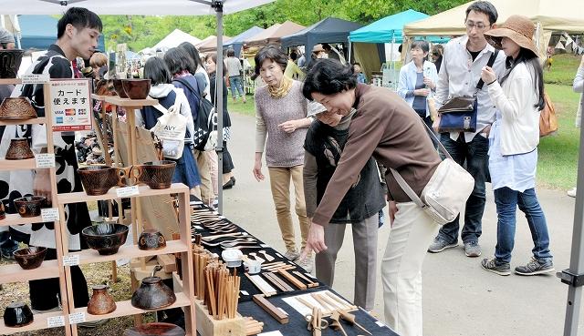 さまざまなジャンルの工芸品が並ぶブースで品定めする買い物客ら=9日、福井県あわら市の金津創作の森