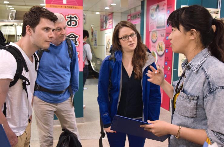 松本駅を訪れた英国人観光客に松本の魅力を尋ねる呉真寧さん(右)