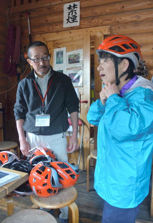 火山館で登山用ヘルメットを借りる女性(右)=9日午前10時27分、御代田町