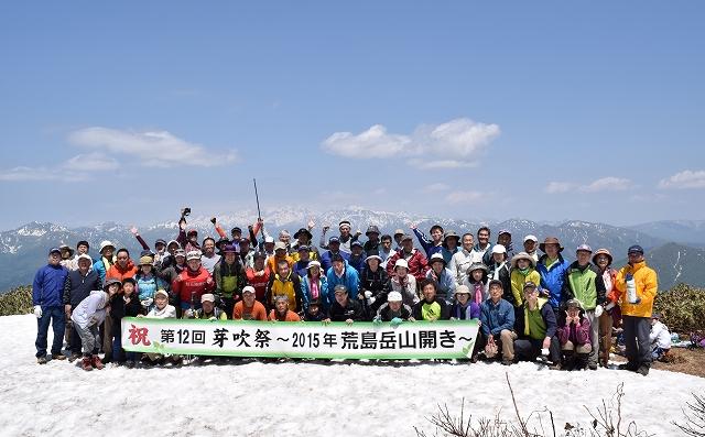 雪の残る山頂で白山などを背景に荒島岳山開きの記念撮影をする登山者=10日、福井県大野市