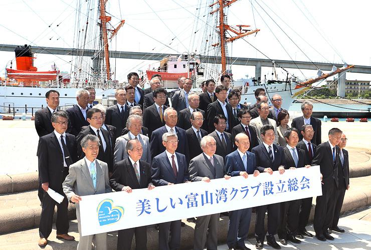 海王丸の前で記念撮影する「美しい富山湾クラブ」役員ら=射水市の海王丸パーク
