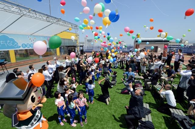 屋上広場の開放を祝い、風船を飛ばす参加者=2014年5月28日、福井市の西武福井店