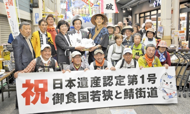 ゴールの出町商店街で、日本遺産認定を祝う横断幕を掲げる松崎市長(中央)や参加者=10日、京都市上京区