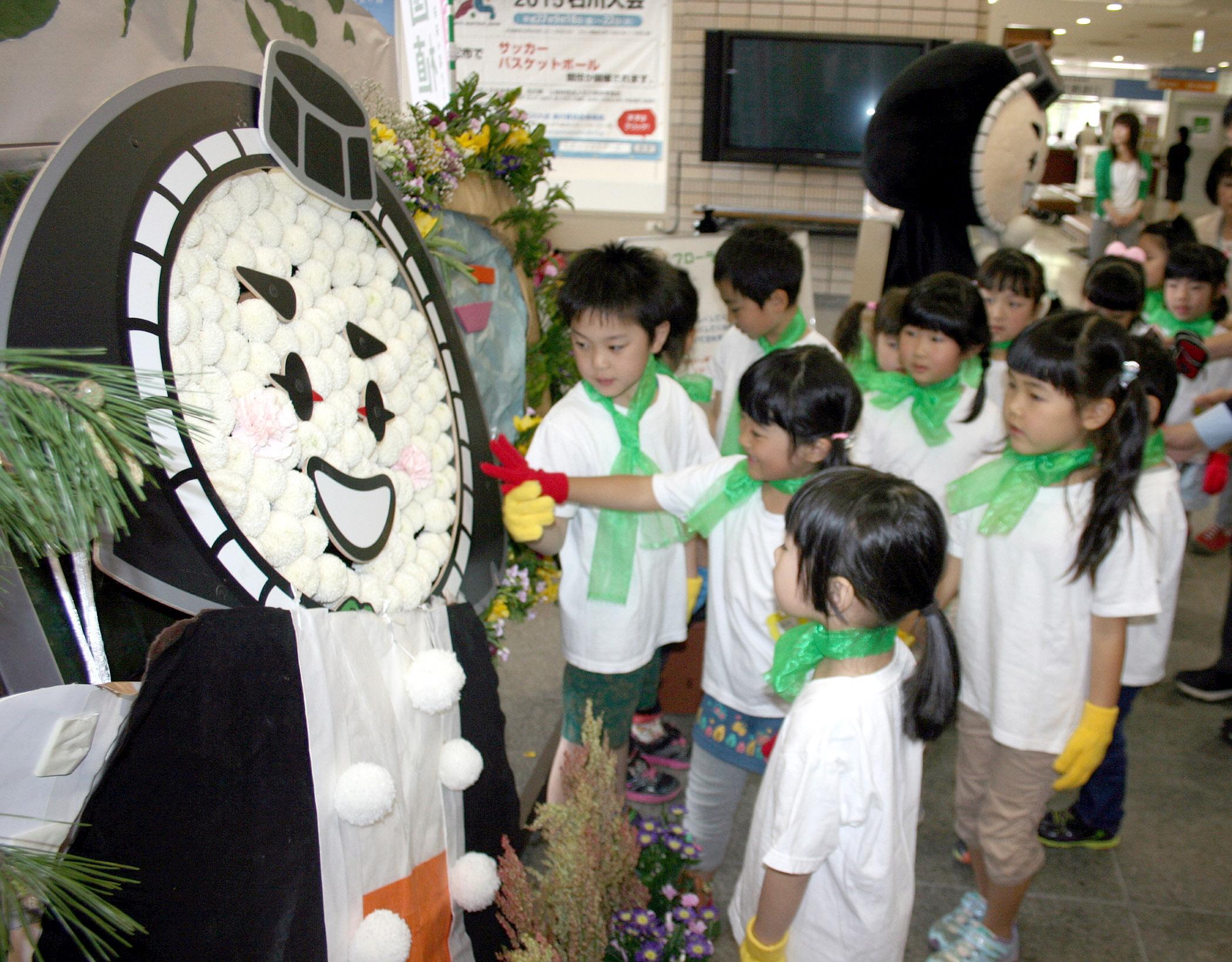 フラワーアートを見る園児=小松市役所