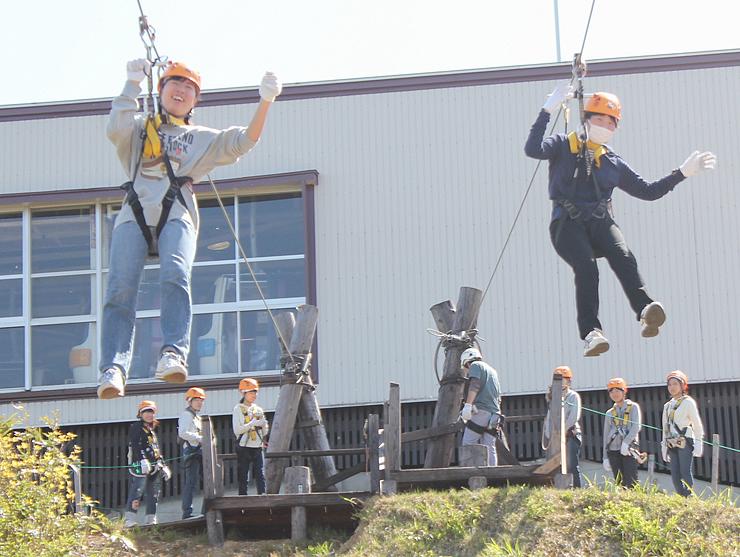 ジップラインで滑空を楽しむ生徒