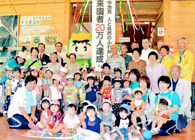 くす玉を割り節目を祝う園児ら=14日、福井県敦賀市の中池見湿地