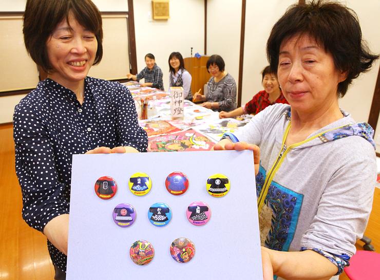 土産品の新商品として製作している法被や武者絵をデザインした缶バッジを見せる小松さん(左)と橋本さん