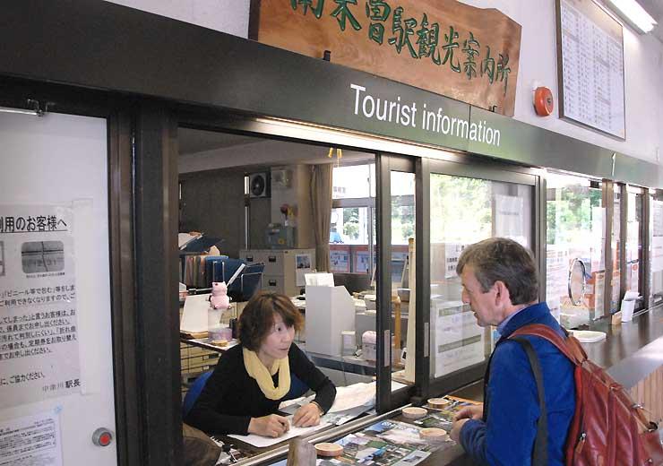 南木曽駅の観光案内所で外国人客に対応する楯さん(左)