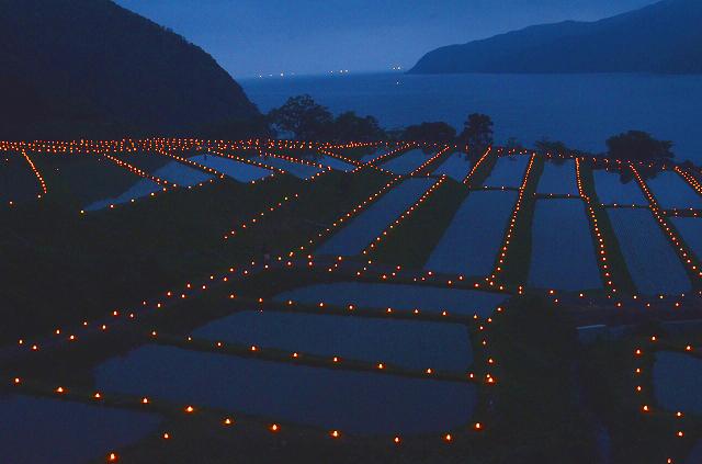 2500本のキャンドルの明かりに彩られた棚田=16日午後7時15分ごろ、福井県小浜市田烏